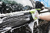 Hands hold sponge for washing car — Stock Photo