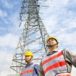 Two workers standing before electrical power tower — Stock Photo