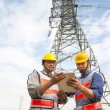 Two workers standing before electrical power tower — Stock Photo #37698805