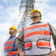 Two workers standing before electrical power tower — Stock Photo #37698807