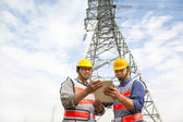 Dwóch pracowników stojących przed energii elektrycznej wieża — Zdjęcie stockowe