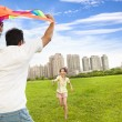 Happy family playing colorful kite in the city park — Stock Photo