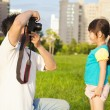 Happy father taking picture with little girl in the city park — Stock Photo