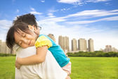 Smiling little girl sleeping on father shoulder at city park — Stock Photo