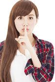 Giovane e bella donna con un dito sulle labbra — Foto Stock