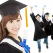 Young graduate girl student holding diploma with classmates — Stock Photo