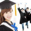 Stock Photo: Young graduate girl student holding diploma with classmates