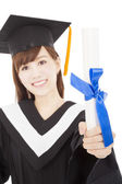 Young graduate girl student holding and showing diploma — Stock Photo