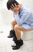 Business man with frustrated expression sitting toilet seat — Zdjęcie stockowe