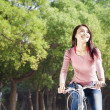 Pretty young woman riding bike in the park — Stock Photo #39133141