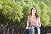 Pretty young woman riding bike in the park — Stock Photo