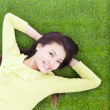 Beautiful young woman laying down in park — Stock fotografie