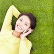Stock Photo: Womsmiling happily on phone while lying grassland