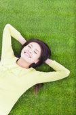 Smiling woman lying on the grassland — Stock Photo
