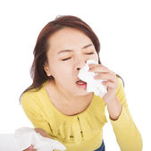 Young woman with a an allergy sneezing into tissues — Stock Photo