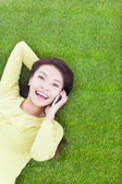 Smiling young woman lying with cell phone on green meadow — Stock Photo