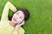 Smiling young woman listening with cell phone on grassland — Stock Photo
