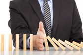 Businessman hand stop dominoes continuous toppled — Stockfoto