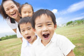Asian smiling family playing on meadow and sunny day — Stock Photo