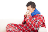 Ill man blowing nose with tissue on sofa — Stock Photo