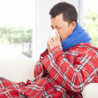 Ill man blowing nose with tissue on sofa at home — Stockfoto