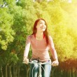 Pretty asian young woman riding bike in the park — Stock Photo #39940271