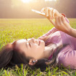 Smiling young woman touching cell phone and lying on meadow — Stock Photo #39986965