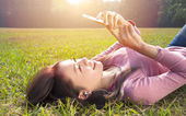 Smiling young woman touching cell phone and lying on meadow — Stock Photo