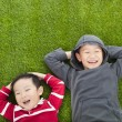 Two brothers lying on the meadow in the park — Stock Photo