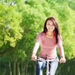 Young woman riding bike and listening music — Stock Photo