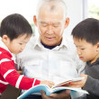Stock Photo: Grandfather and grandchildren reading a book