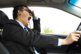 Exhausted driver yawning and driving car — Stock Photo