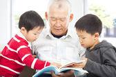 Grandfather and grandchildren reading a book — Stock Photo