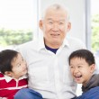 Happy grandfather and grandchildren playing at home — Stock Photo
