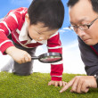 Father and kid with magnifying glass to discover — Stock Photo