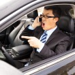 Stock Photo: Irate businessmtalking with cell phone in car