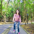 Pretty Woman riding a bike on the forest trail — Stock Photo