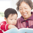 Grandmother and grandson are reading story book together — Stock Photo #40575469