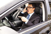 Irate businessman talking with cell phone in the car — Stock Photo