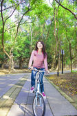 Pretty Woman riding a bike on the forest trail — Foto Stock
