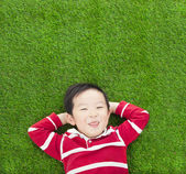 A funny kid lying and holding his head — Stock Photo