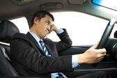 Depressed businessman holding head and driving car — Stock Photo