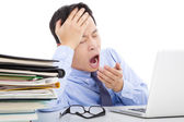 Exhausted young businessman yawning and holding his head — Stock Photo