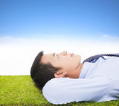Young businessman lying on a meadow and contemplating — Stock Photo