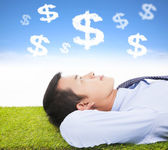 Businessman thinking money and goal on a meadow — Stock Photo