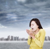 Young woman blowing to warm hands up with black clouds — Stock Photo