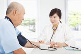 Doctor measuring blood pressure of senior man at home — Stock Photo
