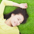 High angle view of a young woman listening music on grass — Stock Photo