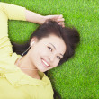 Pretty woman listening music and lying on a meadow — Stock Photo #41170077