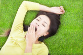 Smiling  woman yawning  and lying on grass  — Stock Photo